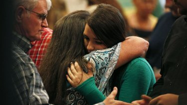 Lacey Scroggins, right, embraces a  woman at a church service in Roseburg on Sunday.