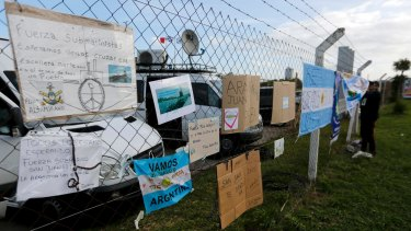 Signs with messages in support of the crew of the Argentine submarine ARA San Juan hang from the fence at the naval base after the vessel vanished last week.