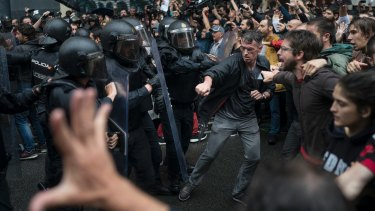 Catalans confront Spanish riot police near a voting site in Barcelona on polling day, October 1.