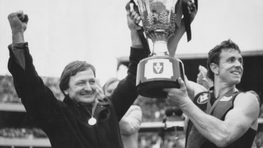 Doubling up: Kevin Sheedy and Terry Daniher lift the 1985 premiership cup.