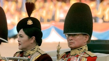 Thai King Bhumibol Adulyade and Queen Sirikit review the honour guard in 1999.