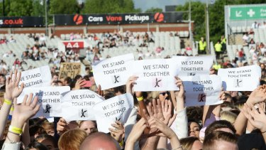 """People in the One Love Manchester concert crowd hold placards reading """"We Stand Together""""."""