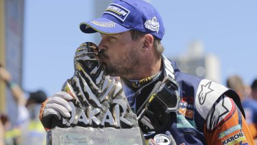 Sealed with a kiss: Toby Price with his 2016 Dakar Rally winner's trophy in Rosario, Argentina.