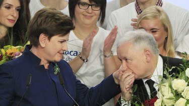 Conservative Law and Justice leader Jaroslaw Kaczynski  kisses the hand of his party's candidate for prime minister, Beata Szydlo, after early results show victory for the Eurosceptic side.