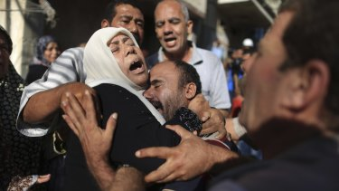 July 2014: Members of the Bakr family mourn during the funeral in Gaza City for four of their children killed on the beach by an Israeli strike.