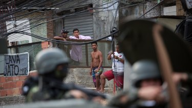 Residents look at an armoured vehicle patroling the Rocinha favela, in Rio.