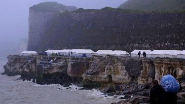 Migrants look out from a new makeshift camp perched along the storm-hit cliffs near Dieppe, northern France, overlooking the English Channel, last week.  A group of around 150 Albanian migrants have set up a tented encampment hoping to cross to the UK.
