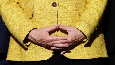 Angela Merkel pauses in her trademark hand gesture.
