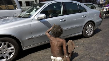 A man begs for money from a passing car in New Delhi. The gap between India's rich and poor has become a potent theme for politicians.