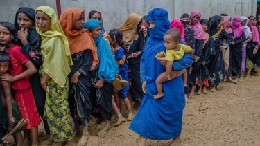 Rohingya women and children wait to collect material for shelters at a refugee camp in Bangladesh.