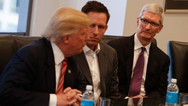Apple CEO Tim Cook, right, and PayPal founder Peter Thiel, centre, listen as Donald Trump speaks during a meeting with technology industry leaders at Trump Tower in New York in December.