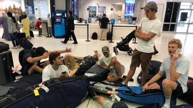 A group of surfers from Sydney wait for updates on their cancelled flight to Sumatra via Denpasar.