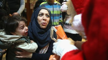 Syrian refugee Ola Hussain apologises to a volunteer dressed as Santa Claus as her one-year-old son Mohamed cries out in fear at a migrant shelter in Berlin.