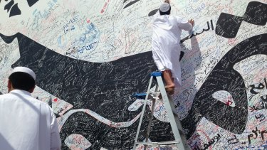 A boy writes a comment on a wall with a depiction of Qatar's emir, Sheikh Tamim bin Hamad Al Thani, that has attracted signatures and comments of support from residents, amid the diplomatic crisis.