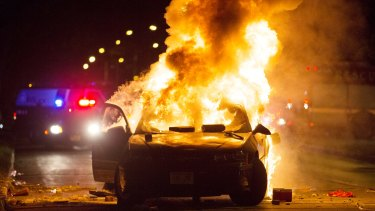 A car burns as a crowd of more than 100 people gathers following the fatal shooting of a man in Milwaukee.
