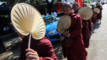 Buddhist monks walk past the National League for Democracy (NLD) headquarters on Monday.