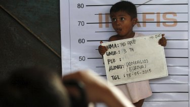 A Rohingya child who recently arrived by boat has his picture taken for identification purposes at a shelter in Kuala Langsa.