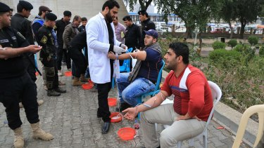 People donate blood for wounded Iraqi security forces fighting against the Islamic State group in Tahrir Square, Baghdad, Iraq, on Saturday.