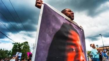 John Thompson carries a large photo of his friend Philando Castile during a demonstration on Sunday.