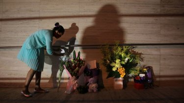 A young girl leaves flowers at the front of NSW Police Headquarters in memory of police employee Curtis Cheng.
