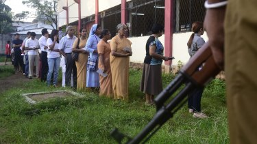 People queue to vote as police stand guard in Colombo.