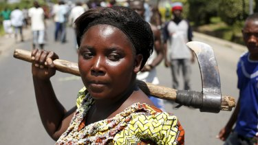 A female protester holds an axe during a protest against Burundian President Pierre Nkurunziza's decision to run for a third term in Bujumbura, Burundi on Wednesday.