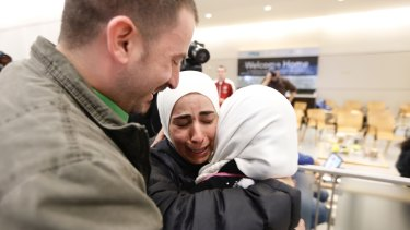 Hisham, left, and Mariam Yasin, centre, welcome their mother Najah al-Shamieh, from Syria, after immigration authorities released her at Dallas-Fort Worth Airport on Saturday.