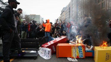 A pile of burning newspaper machines at a demonstration against Donald Trump's inauguration in Washington.