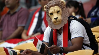 An Iraqi supporter sports a lion's mask and holds flags in both hands as he urges his team on.