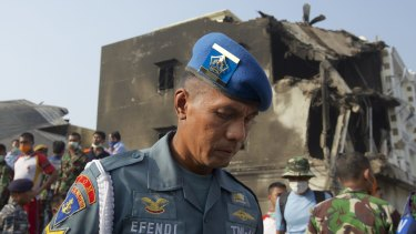A member of the Indonesian Air Force looks over the wreckage of a military transport plane which crashed into a building on June 30, 2015 in Medan.