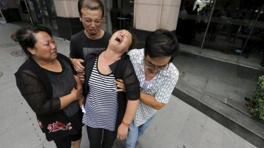 The mother (centre) of missing firefighter Xue Ning is helped by other family members as she cries after trying to demand more information from government officials.