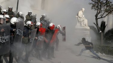 An anti-establishment protester tries to attack riot police during a protest against high-security prisons in Athens.