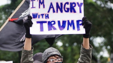 People hold placards during a protest against US President Donald Trump and his recent policies outside of the American Embassy in Jakarta.
