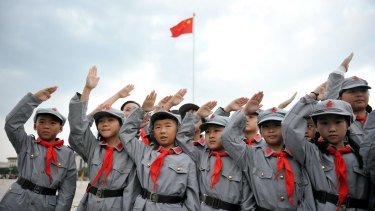 Chinese pupils dressed in Red Army costumes salute.
