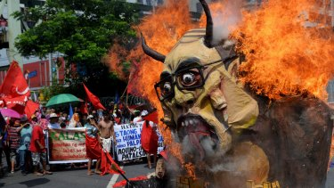 Protesters burn an effigy of President Benigno Aquino III during a rally in Manila on Monday.