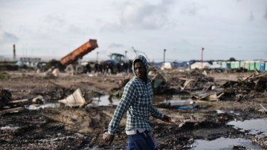 A migrant walks in a street of the makeshift Calais camp on Thursday.