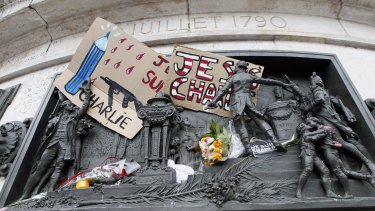 A placard with a news cartoon by French cartoonist Plantu is seen placed amongst other tributes on the statues at the Place de la Republique in Paris.