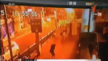This image taken from security footage provided by Thai PBS shows the moment of an explosion in central Bangkok. It shows the bottom of the overheard walk-way used by Jimmy Barnes and his family.