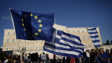 A protester holds a Greek and an EU flag during a pro European Union (EU) demonstration in Athens on Monday.