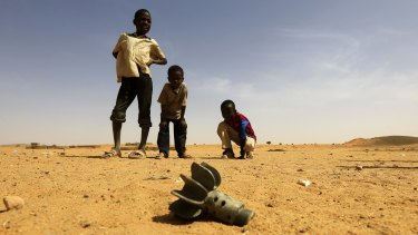 Children look at the fin of a mortar projectile that was found at the Al-Abassi camp for internally displaced persons, after an attack by rebels, in Mellit town, North Darfur, Sudan.