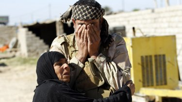 A resident welcomes a relative fighting with the Hashid Shaabi militia, in the town of Al-Alam.