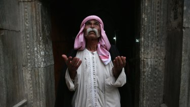 Sheikh Mirza, 84, prays at the entrance to the temple of Lalis, the holiest site of the Yazidi religion last week in Nineveh Province, Iraq.