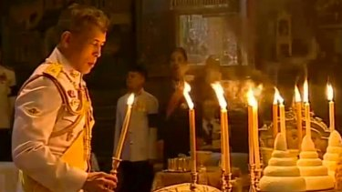 The Thai King lights candles during a religious ceremony at the Grand Palace where the remains of his father lie.