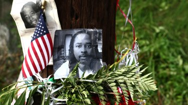 Photos of Samuel DuBose hang on a pole at a memorial near where he was shot and killed.