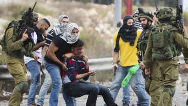 Israeli police provocateurs dressed as Palestinians and Israeli soldiers detain a wounded Palestinian demonstrator during clashes near Ramallah in the Israeli-occupied West Bank.