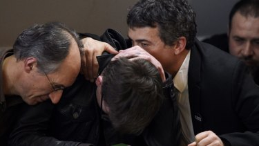 French cartoonist Renald Luzier is comforted by the Editor in Chief of <i>Charlie Hebdo</i>, Gerard Briard (left) and editorialist Dr Patrick Pelloux, during a press conference to present the new issue in Paris.