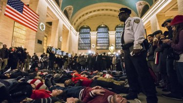 A police officer stands over activists last year staging a die-in and demanding justice for the death of Eric Garner in New York.