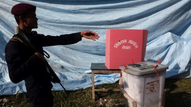 A Nepalese policeman assists voters, unseen, during the legislative elections in Balefi Nepal on Sunday.