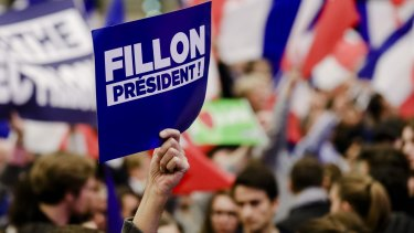 A supporter holds up a sign during an election campaign meeting for Francois Fillon in Paris.