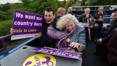 Vote Leave supporters battle with the wind near Sheffield, in England, as they travel on the battle bus of UKIP leader Nigel Farage  campaigning for votes to leave the EU.
